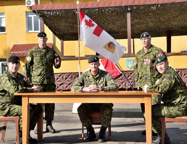 Colonel Michael Blackburn, Reviewing Officer for the Transfer of Command Authority parade, poses for a group photo with the incoming (left) and outgoing (right) Joint Task Force - Ukraine command teams at the International Peacekeeping and Security Centre in Starychi, Ukraine, on March 7, 2017.