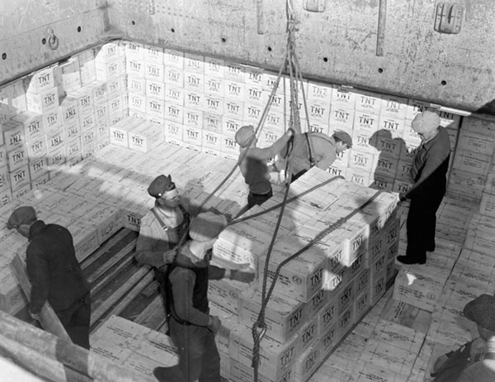 "Longshoremen loading cases of TNT explosives into the hold of an unidentified merchant ship, Halifax, Nova Scotia, November 29, 1942. Unlike other volatile components, Bob Mercer asserts that ""TNT is extremely insensitive. You could throw a case of it off a two-story building and nothing would happen."" (library and archives canada, mikan 3572366)"