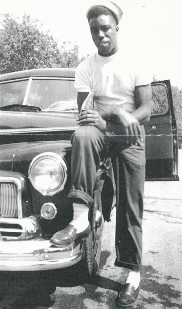 Post war, Randolph Hope is leaning on a car he rented to drive to Montreal, Quebec.
