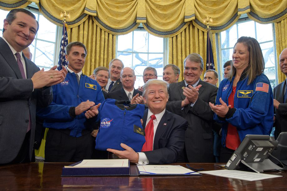 "On March 21, 2017 U.S. President Donald Trump held up his new honorary NASA flight jacket, given to him by the chief of NASA's Astronaut Office and former Navy SEAL Chris Kassidy (on the left, wearing a blue NASA jacket), during the signing into law of the NASA Transition Authorization Act of 2017. This bill authorizes the agency to ""keep doing what it's been doing for the past seven years,"" including working with the private sector. Photo: NASA"