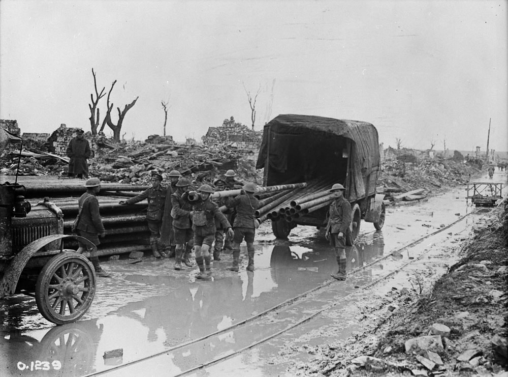 Unloading some of the 70 kilometres of water mains behind the front lines. On the near side of the road, the tracks of a small-gauge railway are visible. The rail cart in the background, designed to carry anything from shells forward to wounded to the rear, was pulled by men, not mules. (library and archives canada, mikan 3521936)