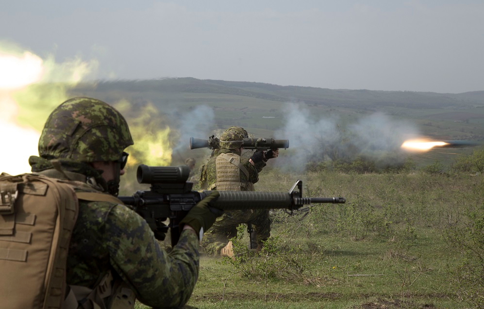 Cincu, Romania. Corporal Michaël Lafrenais-Dietrich of the Voltigeurs de Québec and Private Simon Tremblay of the 1st Battalion, Royal 22e Régiment (in background) fire the Carl Gustav short-range anti-armoured weapon, as Corporal Sonny Gauthier of 5e Ambulance de campagne (in foreground) supports their efforts, during a live-fire frontal assault exercise on a firing range in Cincu, Romania on April 9, 2016 during Operation REASSURANCE. (Photo: Corporal Guillaume Gagnon, Liaison Officer Driver, Operation REASSURANCE Land Task Force)