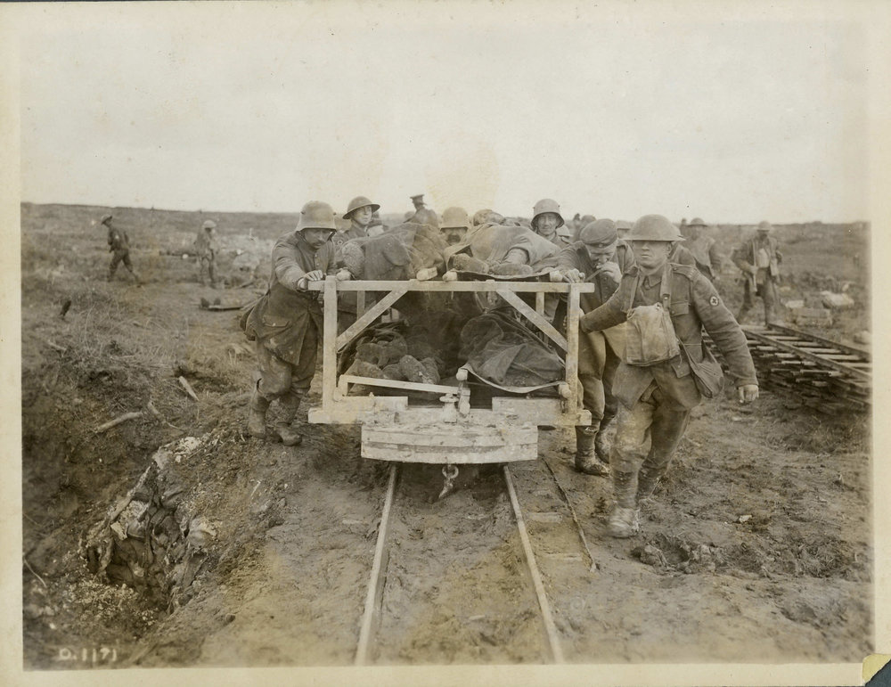 Canadian medical officers (with the Red Cross emblems on the soldiers at right and to the left rear of the photo) use German prisoners, destined to captivity, to help transport Canadian casualties from Vimy Ridge, April 1917. They use a two-tiered carrier, pulled along a light railway line leading from the front. Almost 6,000 Germans were captured and thousands of Canadians were wounded on the first day of the battle. (george metcalf archival collection, cwm   19920085-924  )