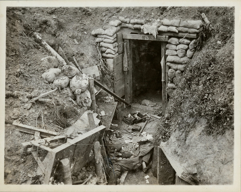 The body of a dead German soldier lies near the entrance to his dugout. While the entrance is intact, the sides of the trench have collapsed. Common items such as an entrenching tool, a water bottle, and ammunition pouches lie scattered on the ground. (george metcalf archival collection, cwm 19920044-195)