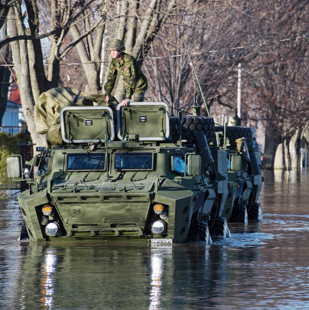 Tactical Armoured Patrol Vehicles patrol flooded streets in Saint-Barthélemy, Québec during Operation LENTUS, May 12, 2017. But is door-to-door searching of neighbourhoods the best use of the military during flooding? Author Eva Cohen believes using the Canadian Armed Forces for these types of events is not the most efficient or cost-effective use of the military and its resources. (Sgt Marc-André Gaudreault, Valcartier Imaging Services)
