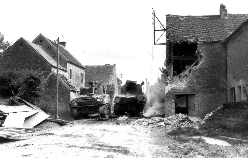 A Sherman burns while a second inches past it. The number 45 painted on the tank designates the vehicles are part of the 29th (SAR) Armoured Reconnaissance Regiment. The fighting devastated the hamlet too. On the left, metal roofing and siding from a collapsed building litter the ground, while the brick building on the right was hit by an AP round. (lt d. grant, dnd, lac)