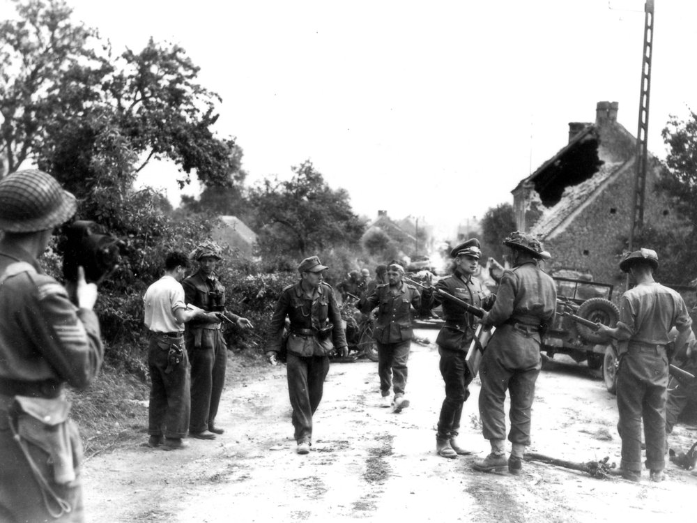 "German prisoners trudge into captivity on August 19, 1944. Major David Currie is third from the left, with pistol in hand. He is talking to Trooper Lowe who had part of his uniform burned off when his machine gun jammed and exploded the day before. This photograph is taken on the Trun–Chambois road, facing south-southeast toward Trun. Official historian C. P. Stacey wrote: ""This is as close as we are ever likely to come to a photograph of a man winning the Victoria Cross."" (lt donald grant, dnd, library and archives canada, pa-  111565  )"