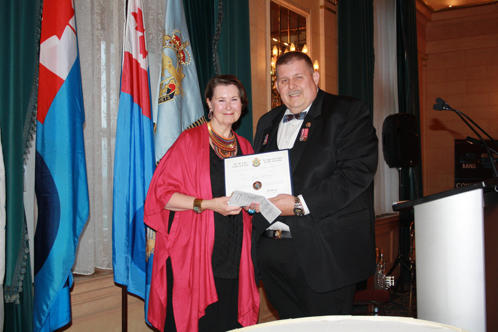 Donald Berrill, National President of the Air Cadet League of Canada, giving a Certificate of Appreciation to Senator Marilou McPhedran.