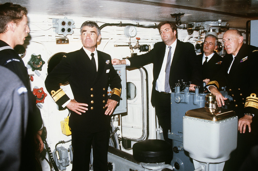 During a cruise around the world, Gunner's Mate First Class V.W. Allen explained operations inside the No. 1 gun turret aboard the battleship USS  Missouri  to officers of the Royal Australian Navy — RAdm D.J. Martin (left) and VAdm M.W. Hudson (right) — and Australian Minister of Defence Kim Beazley (centre). Hudson is recognized for playing an important role in the introduction of the Collins-class submarines, Anzac-class frigates and establishing two-ocean basing for ships of the RAN during his tenure as Chief of Naval Staff from 1985 to 1991. (u.s. navy)