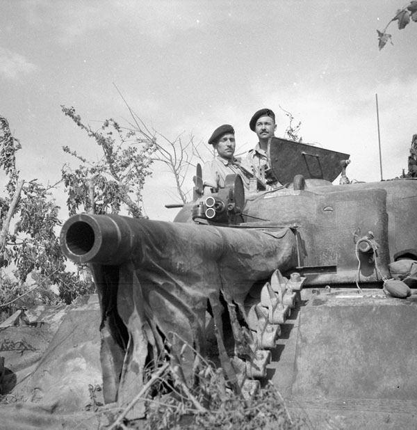 Lt R.O. Campbell (left) of the CFPU and Cpl H.H. Mowbray with a movie camera mounted on the turret of a Sherman tank near the Hitler Line, Italy, May 23, 1944. The CFPU shot groundbreaking footage of the Battle of Ortona, and one cameraman, Sgt Jack Stollery, was awarded the Military Medal for his daring in getting the shot. (lt strathy e.e. smith, pa–  140097  )