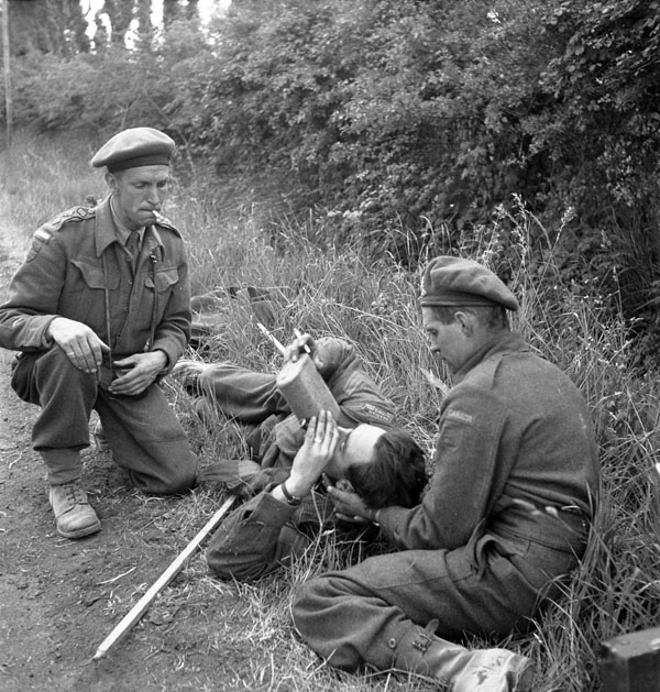 Sergeant W.G. Grant, who has broken his leg, receives assistance from Captain Colin McDougall (left) and Private M.W. Treganza, all of the Canadian Army Film and Photo Unit, Bayeux, France, June 14, 1944. (lt ken bell, dnd, library and archives canada, pa–  152089  )