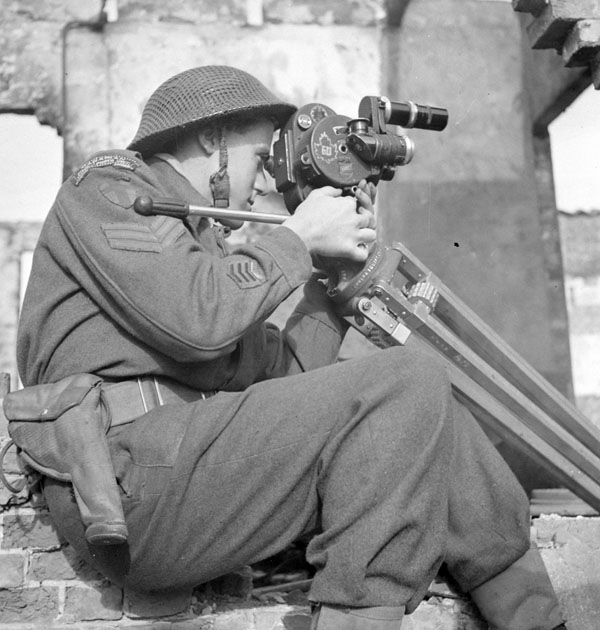 Sergeant Lew E. Weekes of the Canadian Army Film and Photo Unit filming beside a shell-damaged building near Hoogerheide, Netherlands, October 15, 1944. (lt ken bell, library and archives canada, pa–  136214  )