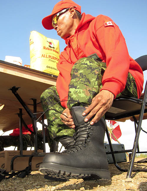 Canadian Forces Ranger Danny Smith from Inuvik, NT tries out new wet weather boots during Operation NANOOK 2012 in Inuvik, Northwest Territories. Military and civilian personnel in the Canadian Armed Forces who require safety footwear not provided by their respective units are now receiving reimbursements for the purchases in a new way. Photo: Sergeant Frank Hudec, Canadian Forces Canada Command. ©2017 DND/MDN Canada.