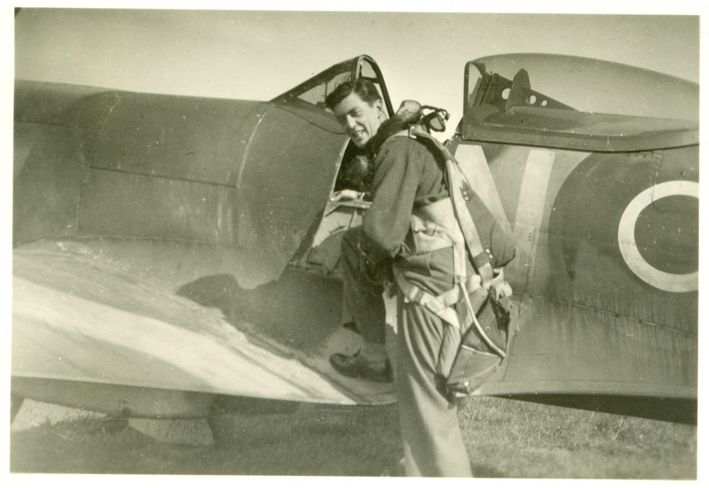 F/O Gordon Hill climbing aboard his Spitfire. A stroke of luck — his non-starting aircraft — ended up saving Hill's life on January 1, 1945.
