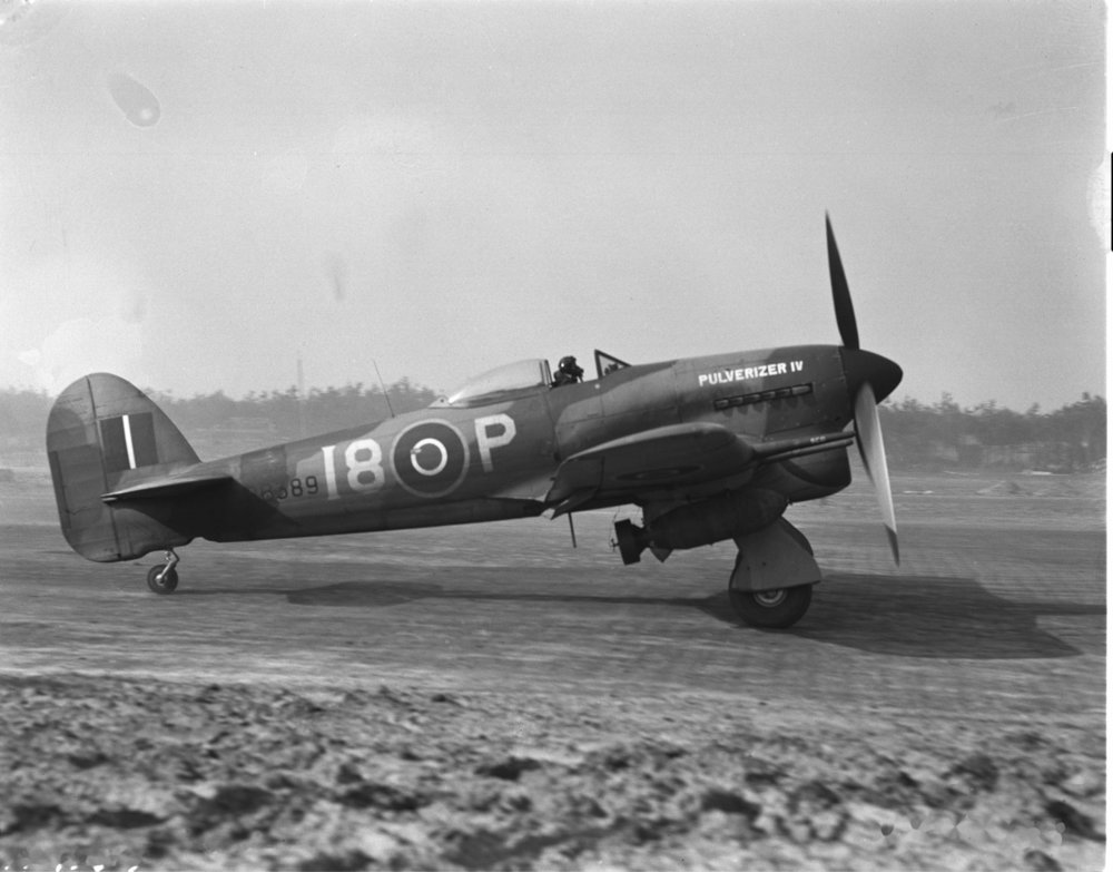 "A No. 440 Squadron Typhoon taxies on operations at Eindhoven, Holland during the spring of 1945. Minutes later, it would have been delivering its two 1000-pound bombs. This Typhoon, christened ""Pulverizer IV,"" was F/L Harry Hardy's last Tiffy of the war. (rcaf)"