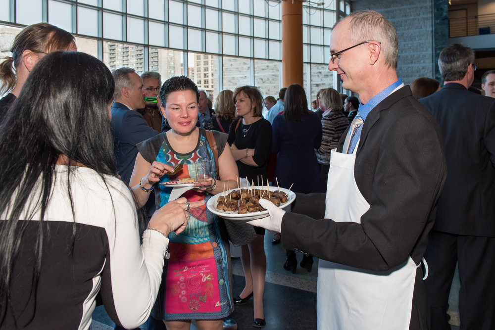 A volunteer server offers food to guests at the reception.