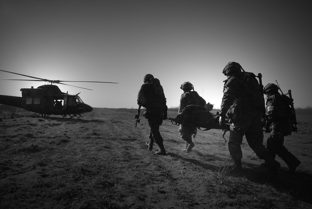 An injured soldier is rushed off the battlefield and onto a CH-146 Griffon helicopter following a firefight in a mock Afghan village during Exercise MAPLE GUARDIAN at CFB Wainright in 2008. Unfortunately, this scenario played out all too often on the real battlefield of Afghanistan. (Cpl Jasper Schwartz, Army News Montreal)