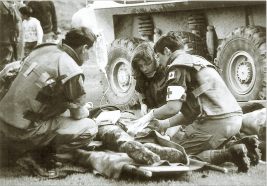 "A Canadian soldier receives medical attention after being injured by a mortar round in Bosnia. Casualty reports were not always made immediately public back in Canada for fear of a negative public impression as the bloody side of ""peacekeeping"" was not the image the government wanted to promote. (dnd photo)"