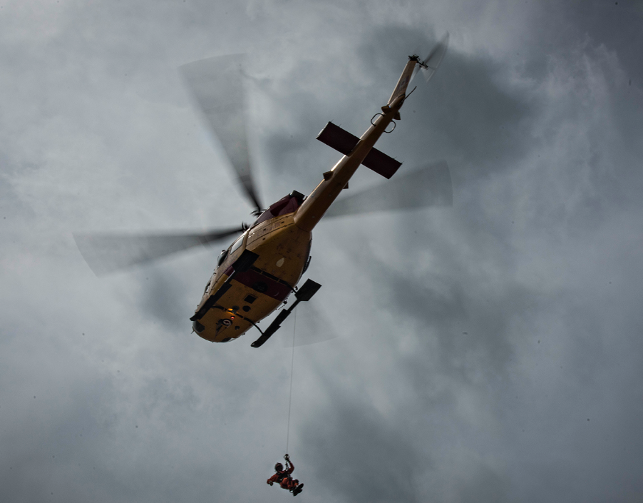 A Search and Rescue Technician is hoisted by a CH-146 Griffon helicopter from 439 Combat Support Squadron during During Chinthex 18, held near Thunder Bay, Ontario. PHOTO: Private Hugo Montpetit