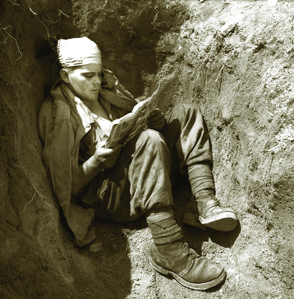 Fighting the boredom that is every infantryman's lot, R22eR private Lambert does some light reading in a rifle pit.   (LIBRARY AND ARCHIVES CANADA 3403685)
