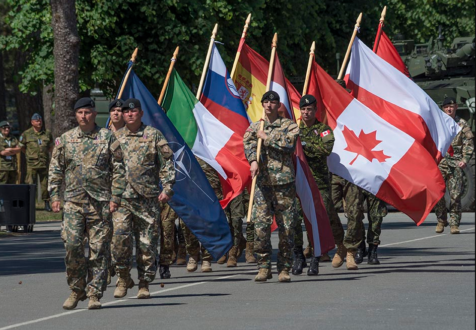 Flag-bearers representing Latvia, Canada, Albania, Italy, Poland, Slovenia, and Spain march past during the ceremony marking the establishment of the NATO enhanced Forward Presence Battlegroup at Camp Ādaži, Latvia on June 19, 2017. Photo: Corporal Colin Thompson, Imagery Technician, Joint Task Force – Europe. ©2017 DND-MDN Canada.