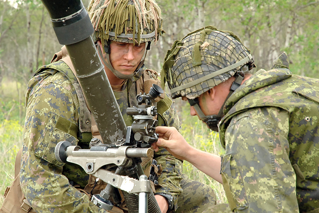 Lieutenant Kevin Little (right) of 1st Regiment, Royal Canadian Horse Artillery, instructs an infantry soldier on how to adjust the sight of an 81-mm mortar system during a training session in June 2018 at Canadian Forces Base Shilo in Manitoba. Photo: Second Lieutenant Ryan Bartlette, 3rd Canadian Division Support Group. ©2018 DND/MDN Canada.