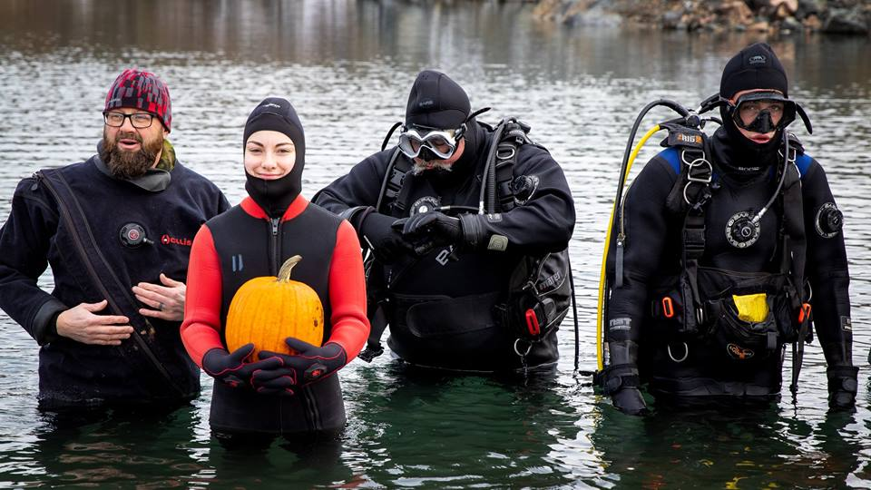 Left to right: Master Warrant Officer (Retired) Chris Hanrahan and daughter Abigail, Pat Bernard and son Dakota prepare to take their pumpkin underwater at Scotch Settlement Quarry near Oromocto, New Brunswick on October 27, 2018. Photo: Marie-Eve Beauchamp.