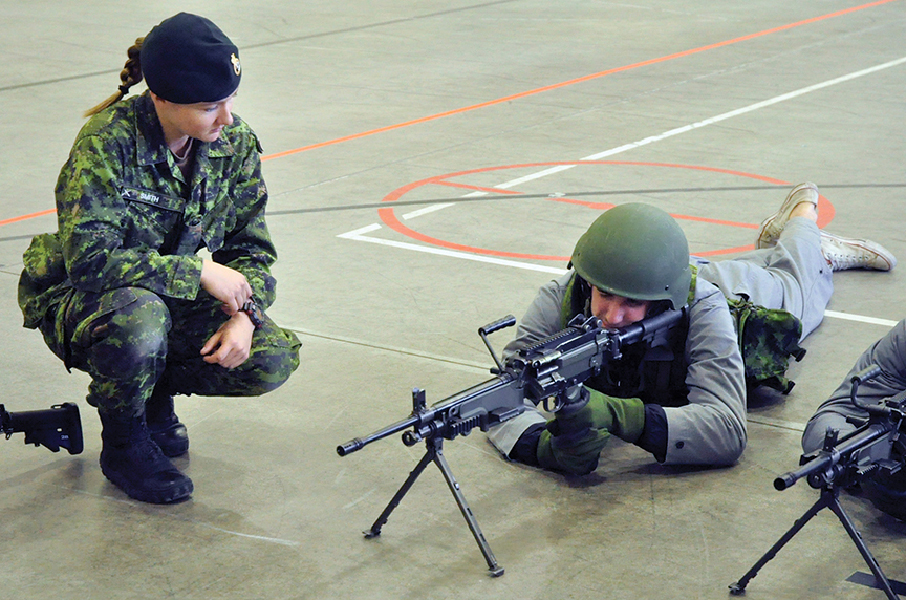 A soldier with 2nd Battalion, Princess Patricia's Canadian Light Infantry instructs a member of the Brandon Wheat Kings hockey team on weapons use during the annual team-building event at CFB Shilo in October 2017. Photo: Jules Xavier, Shilo Stag.