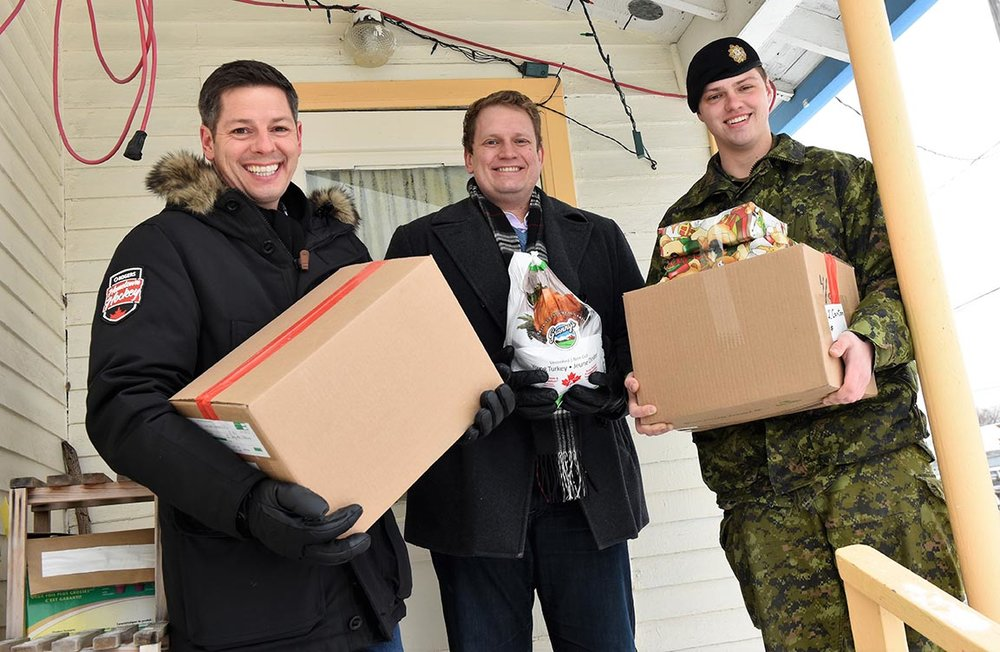 Member of the Legislative Assembly for Kildonan Nic Curry (left), Lieutenant Kyle Atwell of The Fort Garry Horse (right), and Winnipeg Mayor Brian Bowman (centre) deliver hampers on behalf Winnipeg's Christmas Cheer Board during Exercise PARCEL PUSH 2017 on December 16, 2017. Exercise PARCEL PUSH is an annual initiative held by local Canadian Army Reserve units Fort Garry Horse and 38 Combat Engineer Regiment where soldiers deliver holiday hampers to community members in need. Photo: Second Lieutenant Natasha Tersigni, 38 CBG Public Affairs. ©2017 DND/MDN Canada.