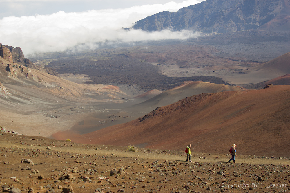 Two hikers descend into Kaupo Gap at Haleakala National Park on the island of Maui, Hawai'i. (Photo by Bill Lascher)
