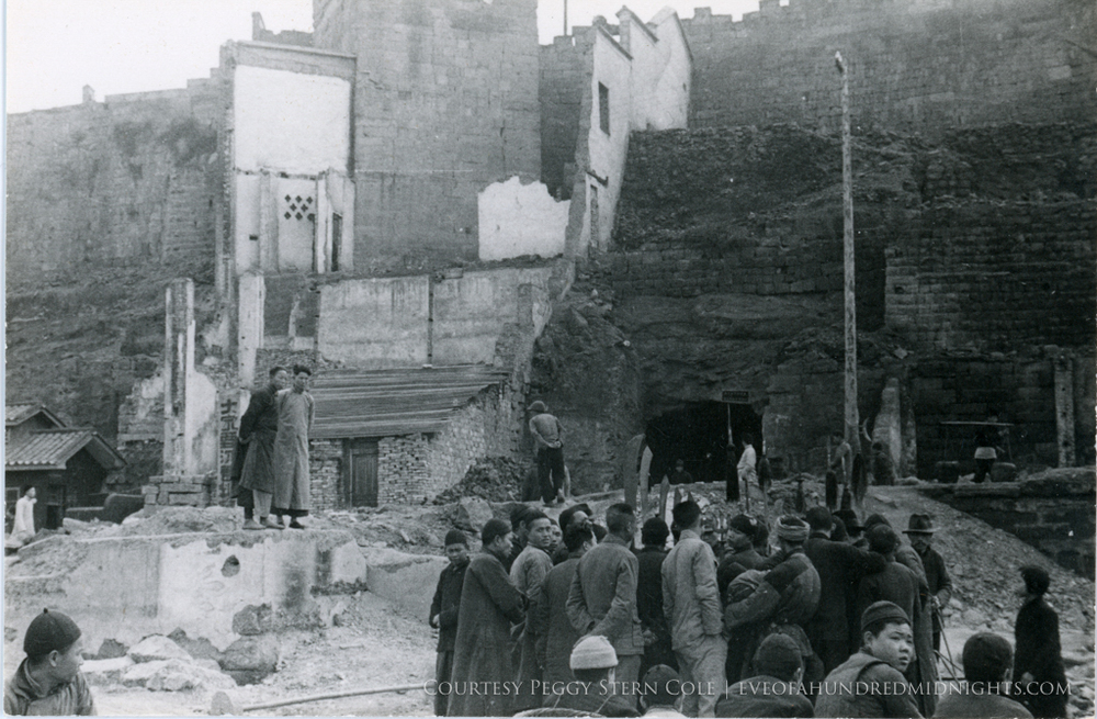 Men gathered with Large sharp Weapons Or Tools Outside destroyed building and air raid shelter.jpg