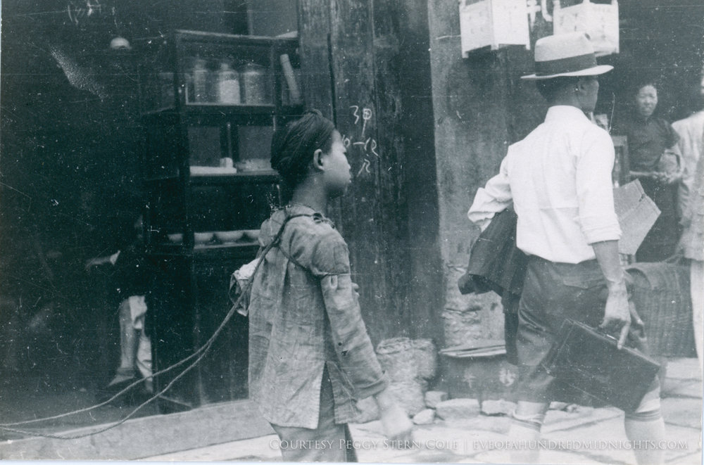 Boy with ropes tied to back on sidewalk.jpg