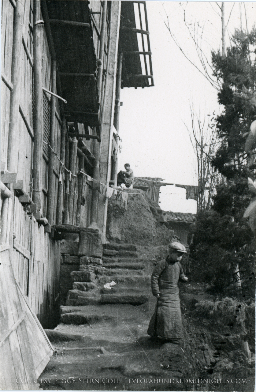 Boy on steps as Woman does washing above.jpg