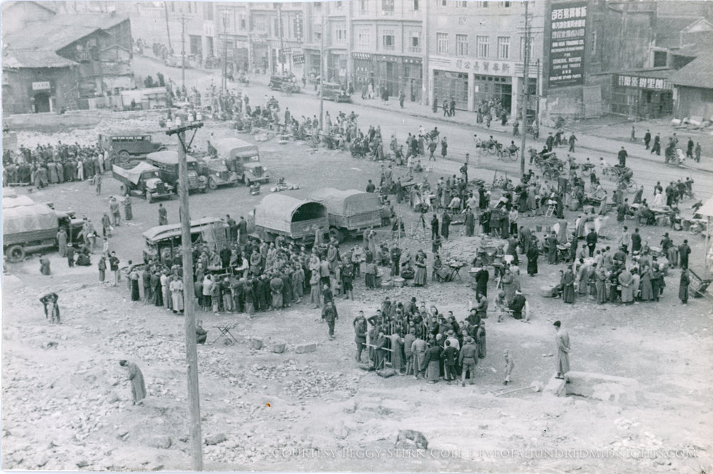 Crowds gathering by trucks beneath hill.jpg