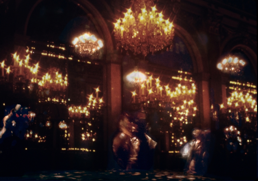 The ball scene, with a  mixture of  projection and real chandeliers.