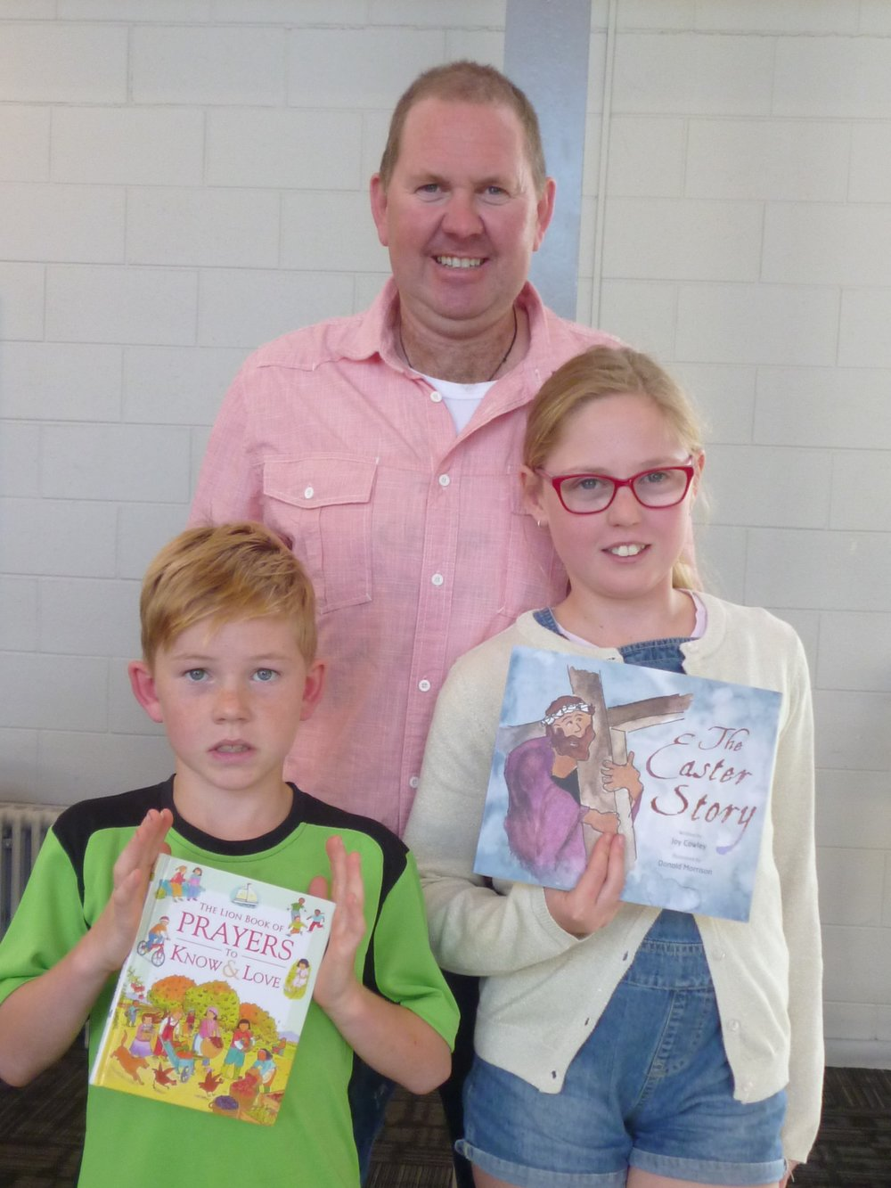 Tim Barker, of Tokanui, with his children Kayden and Kayla show appreciation for books received from Catholic primary schools in our diocese.