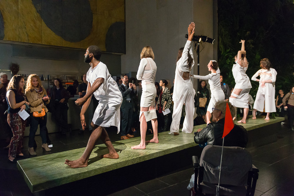 color photo: a group pf people in white in fashion poses standing in a line on top of an elevated platform in an atrium