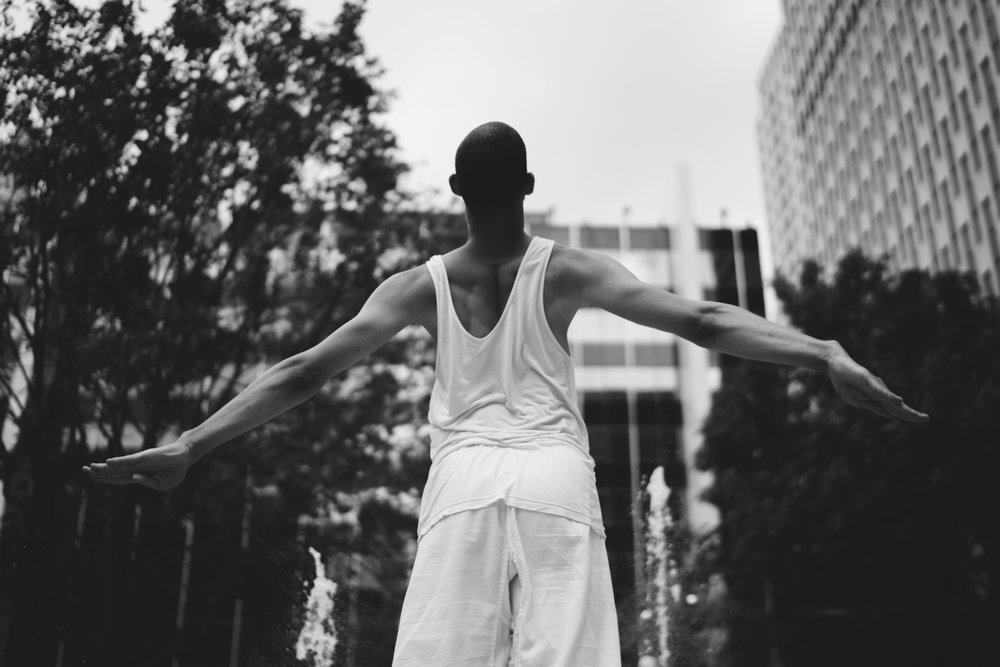 black and white photo of a tall man with his back to us, arms outstretched