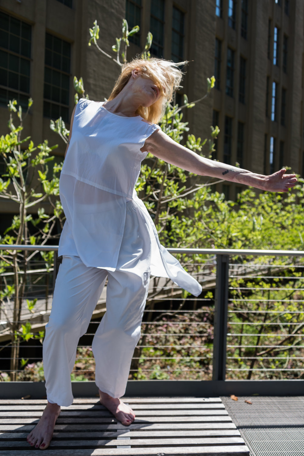color photo: a woman in white standing on a bench in the wind, her arm outstretched