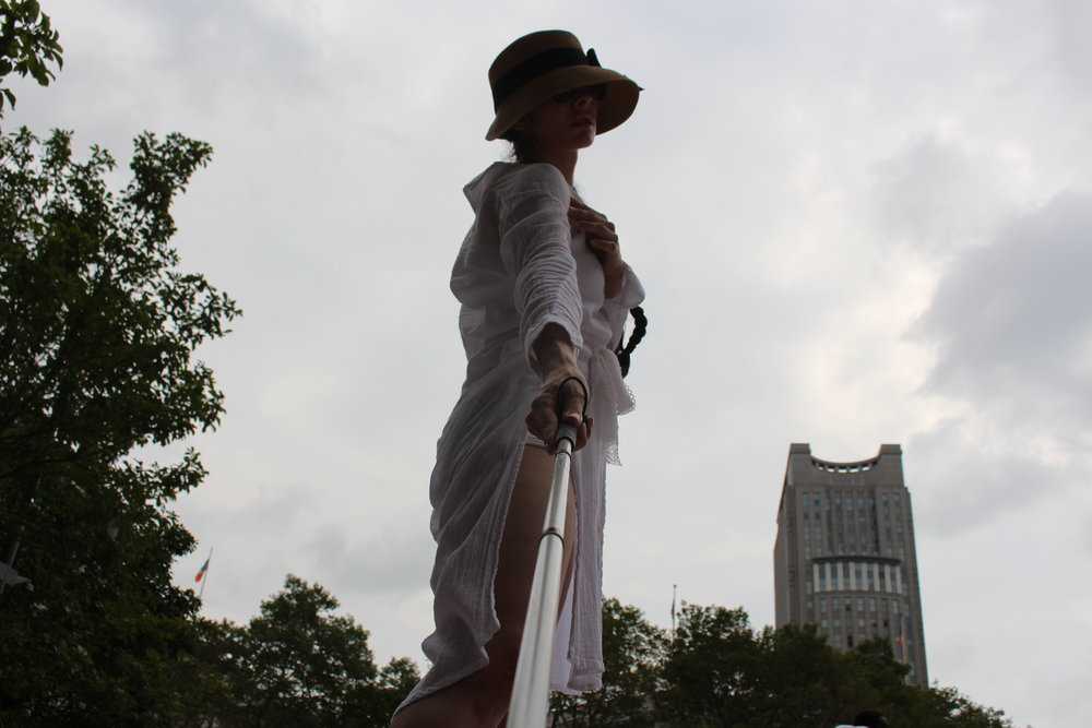 color photo of a woman looking down with a cane outstretched