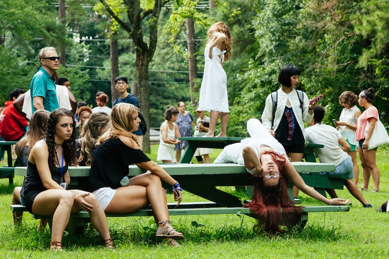 color photo of pedestrians surrounding performers in white. One stands on a bench in a pose, the other leans over the bench looking out