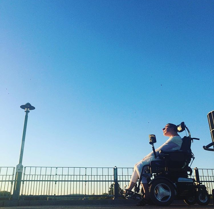 color photo of a woman in a wheelchair holding a pose dressed in white. The angle is low and shows mostly the blue sky above her