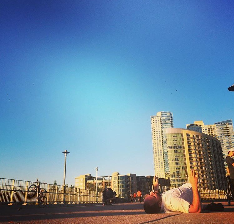 color photo of a man laying on the ground dressed in white looking up to the sky. Tall buildings are in the background