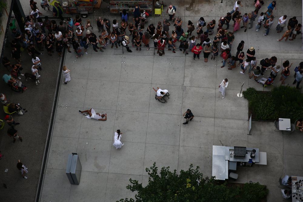 color photo of aerial view of figures in white on concrete pavement surrounded by a large crowd