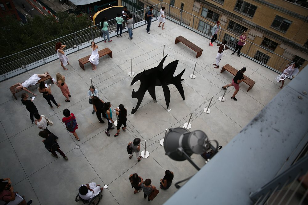 color photo of aerial view of figures in white and others on a concrete balcony. A black piece of art is center