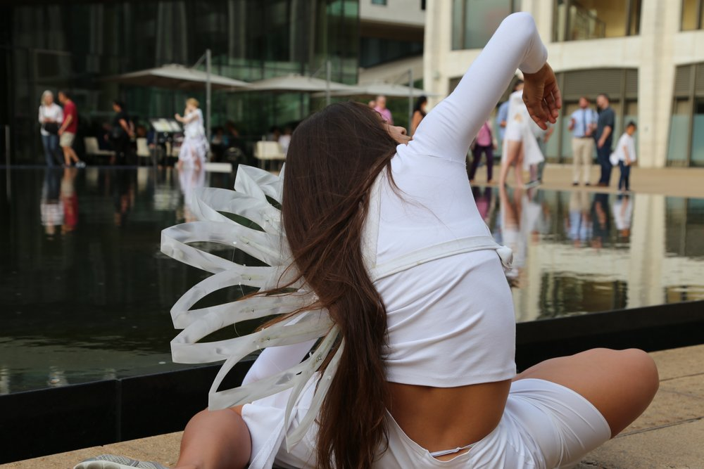 color photo of woman in white with a unfurled shoulder art piece sitting on the ground next to a reflecting pool