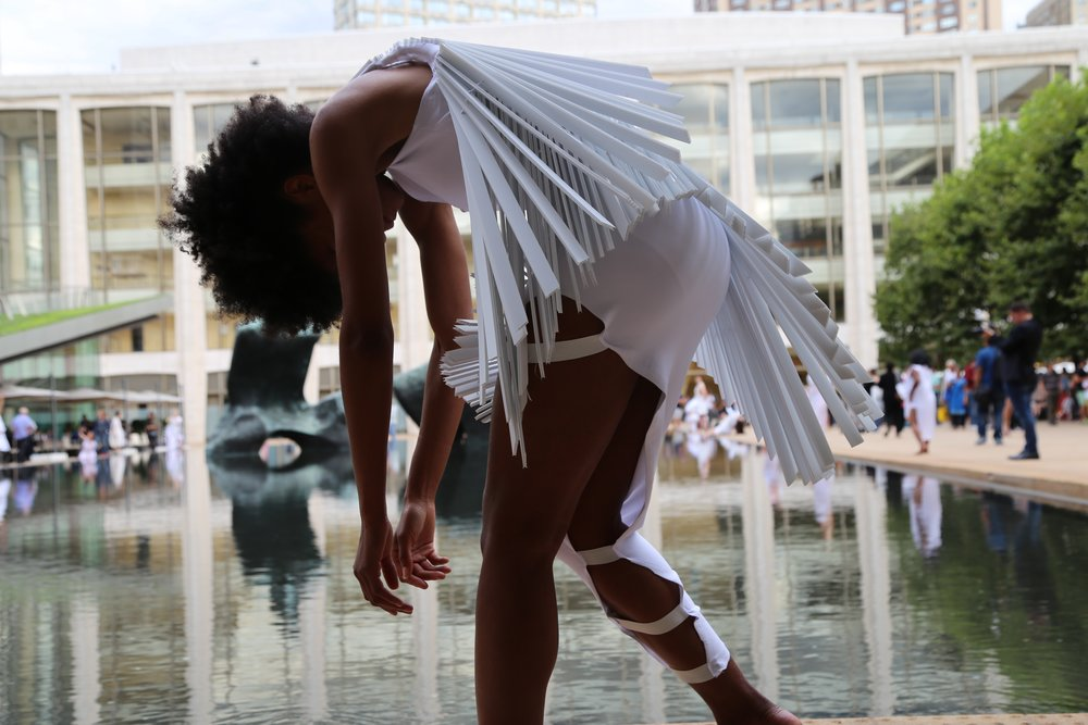 color photo of woman in white unitard with fringes hunched over in front of a reflecting pool