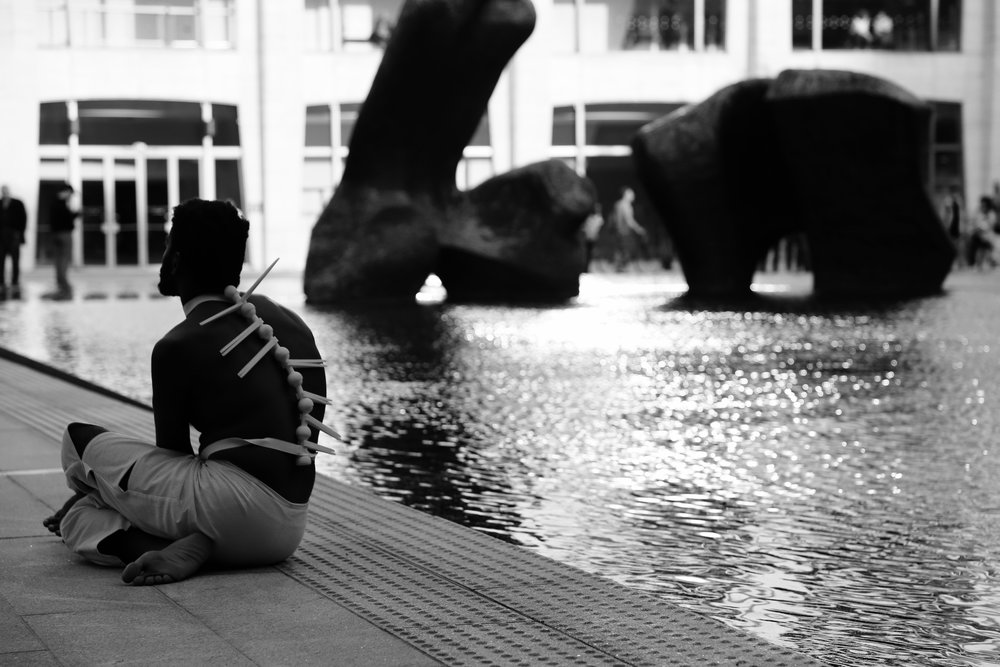 black and white photo of a man sitting along a reflecting pool