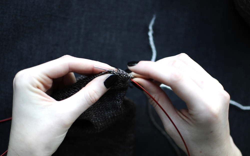 1. Break Yarn A and leave a long tail, approximately three times the circumference of your sock, for sewing down the picot hem. Thread the darning needle with Yarn B. Slowly thread the stitches from your needle onto the darning needle and Yarn B. Work in a clockwise direction.