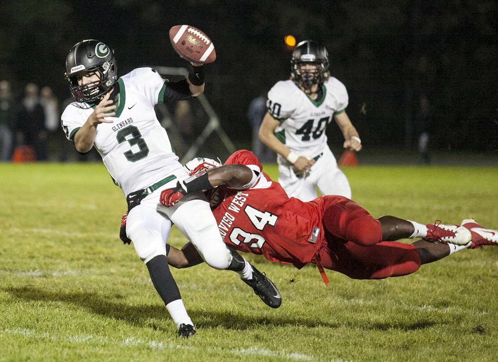 Glenbard West's Henry Haeffner is tackled, as he attempts to throw the ball, by Jamaal Payton during their game on Friday, September 28, 2012, in Hillside, IL.  (For Sun-Times Media)